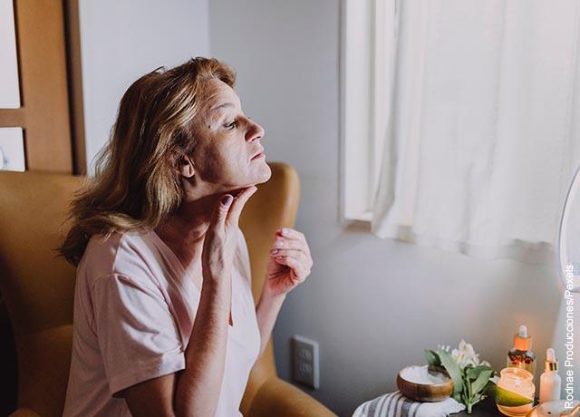 Foto de una mujer aplicando una crema en su piel