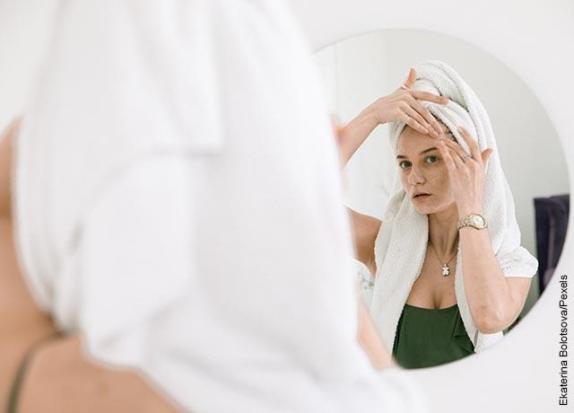 Foto de una joven poniendo crema en su rostro frente al espejo
