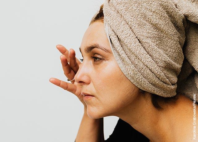 Foto de una mujer apicando un prodcuto cosmético en sus ojos que muestra para qué sirve la mascarilla de carbón