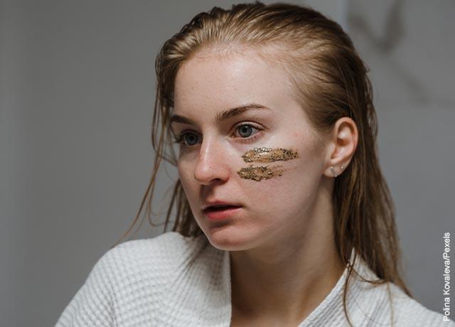 Foto de una joven con crema facial en sus pómulos