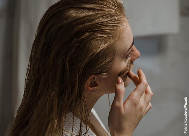 Foto de una joven mujer que pone crema en sus pómulos