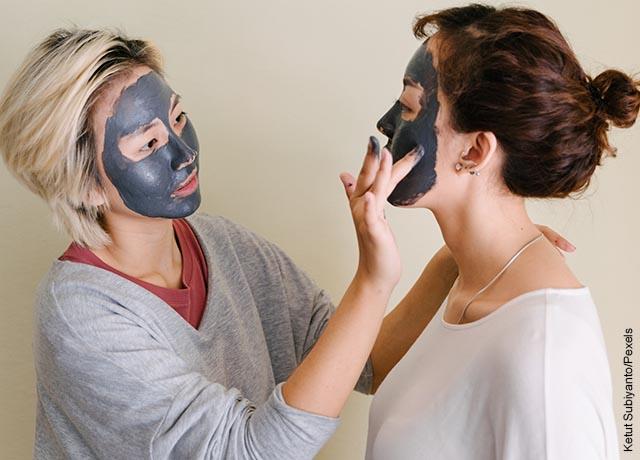 Foto de ds mujeres aplicando una crema negra en su cara