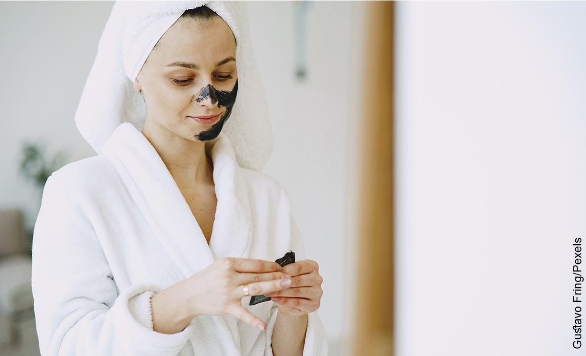 Foto de una mujer aplicando una crema en su rostro que ilustra para qué sirve la mascarilla de carbón