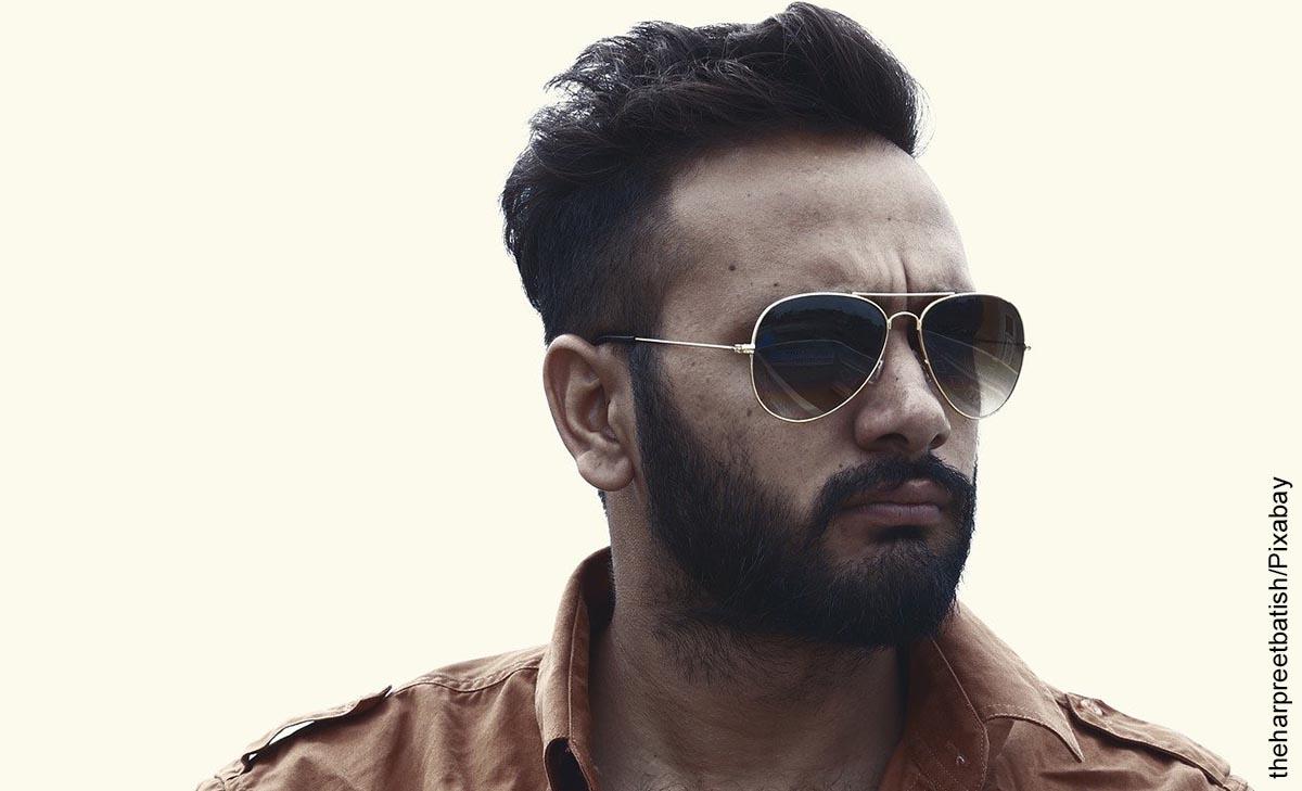 Foto de un hombre con gafas oscuras posando a la cámara que muestra los peinados de cabello corto