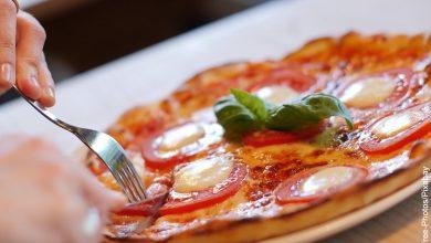 Foto de una mujer cortando una pizza que muestra las recetas vegetarianas