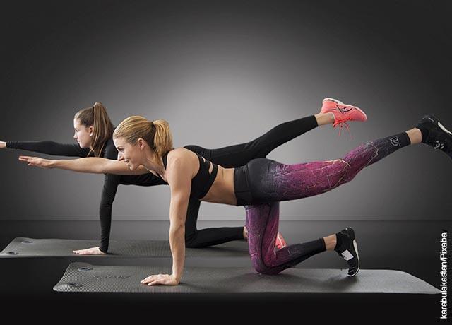 Foto de dos mujeres haciendo estiramientos con sus piernas y brazos