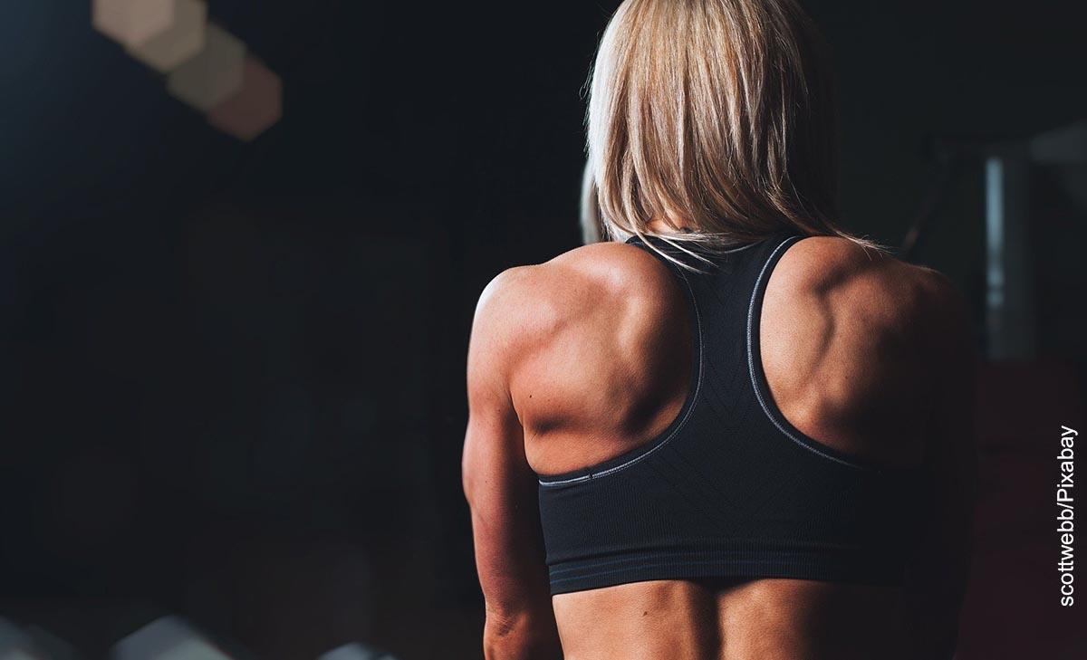 Foto de una mujer gimnasta de espalda que revela rutina de ejercicios en casa para mujeres