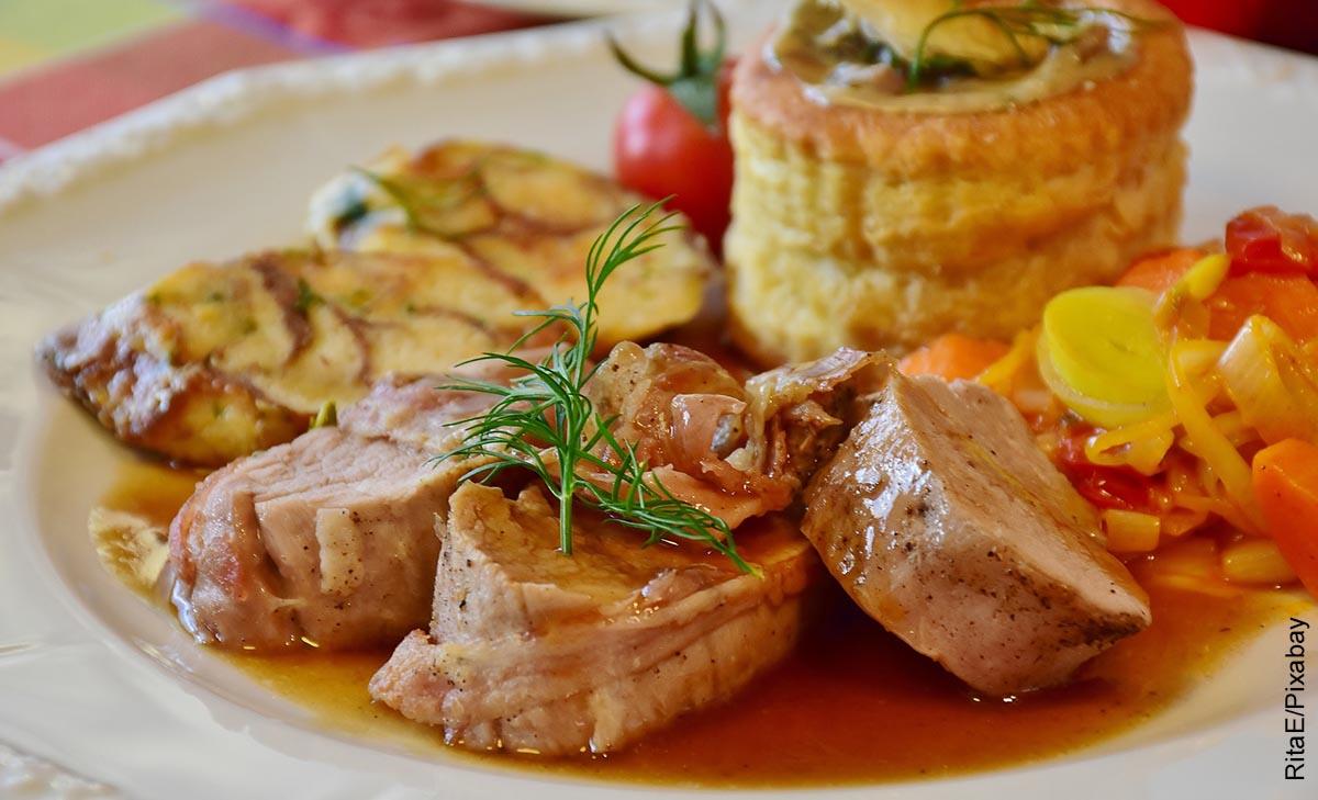 Foto de medallones de solomillo de cerdo con verduras en un plato