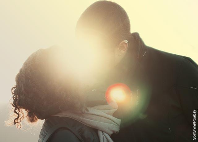 Foto de una pareja besándose al aire libre