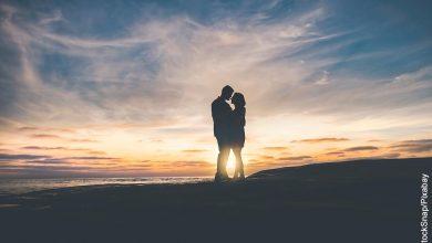 Foto de una pareja abrazada en la playa que muestra lo que es soñar con besar a un hombre