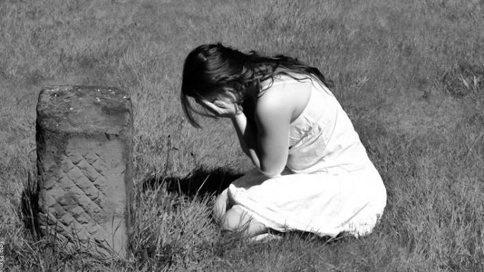 Foto de mujer llorando en cementerio