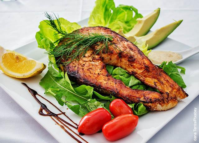 Foto de un pescado asado con verduras en un plato