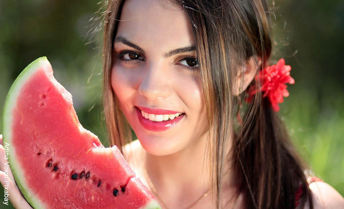 Foto de una mujer sonriente comiendo patilla que muestra lo que es soñar con comida