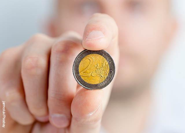 Foto de una mano sosteniendo una moneda