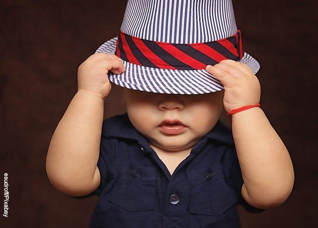 Foto de un bebé poniéndose un sombrero que ilustra lo que es soñar con niños pequeños