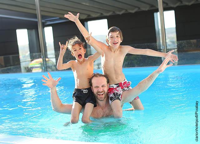 Foto de un padre y sus hijos jugando en el agua