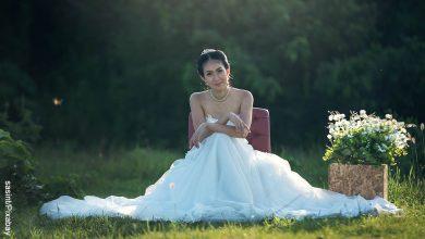 Foto de una mujer sentada en una bosque que ilustra lo que es soñar con vestido de novia
