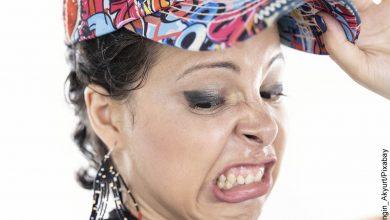 Foto de una mujer con cara de desagrado que muestra lo que es soñar con vómito