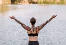 Foto de una mujer practicando yoga frente a un lago que ilustra los tatuajes en la espalda