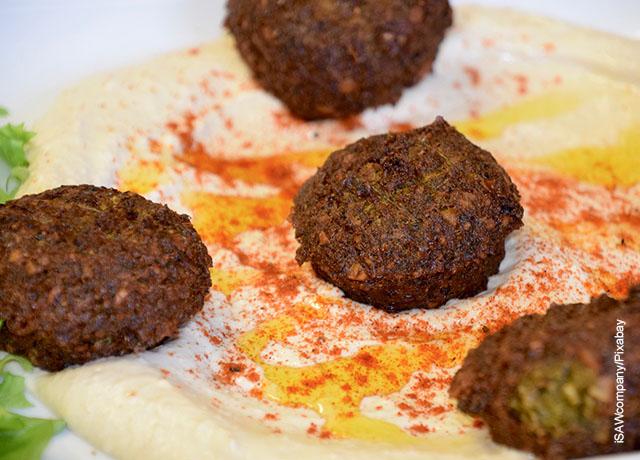 Foto de varios trozos de falafel sobre una salsa blanca