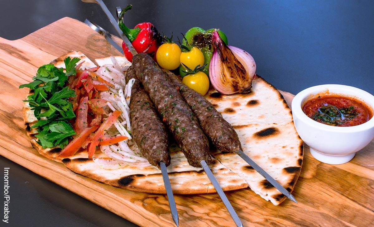 Foto de pinchos, una pan y vegetales sobre una tabla de madera que muestra la comida árabe y sus recetas