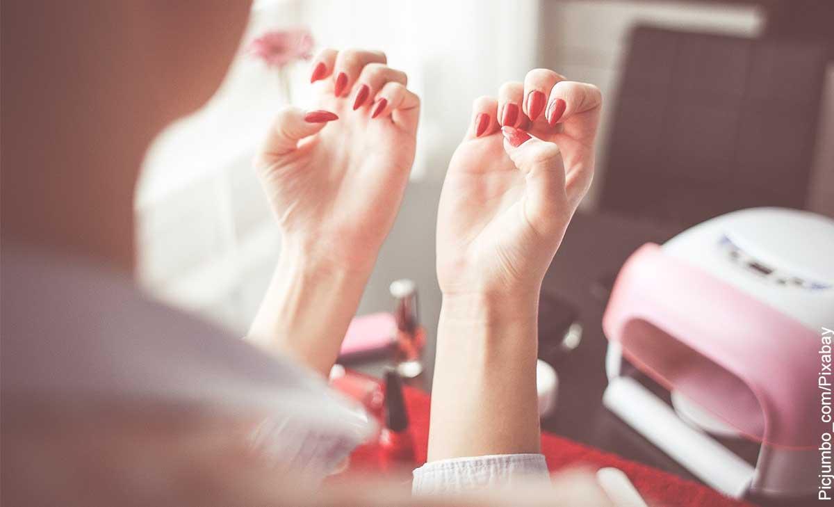Foto de una mujer mirando sus manos que muestra cómo hacer que crezcan las uñas