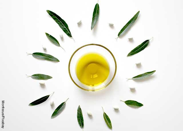 Foto de un recipiente de vidrio con aceite de oliva con hojas de menta