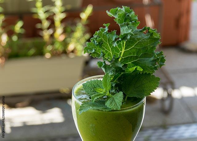Foto de un vaso de jugo verde con hierbas aromáticas por encima