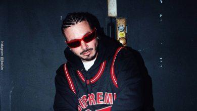 Foto de J Balvin con trenzas y gafas negras y camisa deportiva