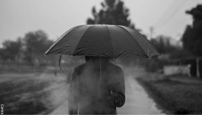 Foto de un hombre con sombrilla bajo la lluvia