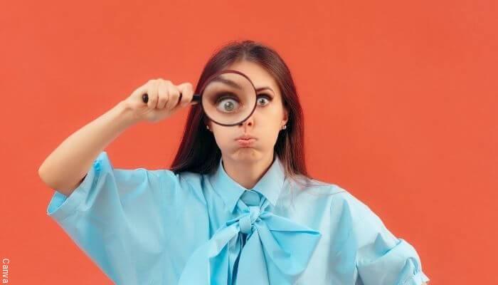Foto de una mujer mirando a través de una lupa
