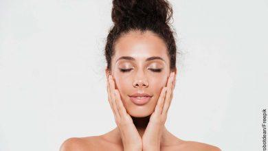 Foto de una mujer tocando su rostro con los ojos cerrados