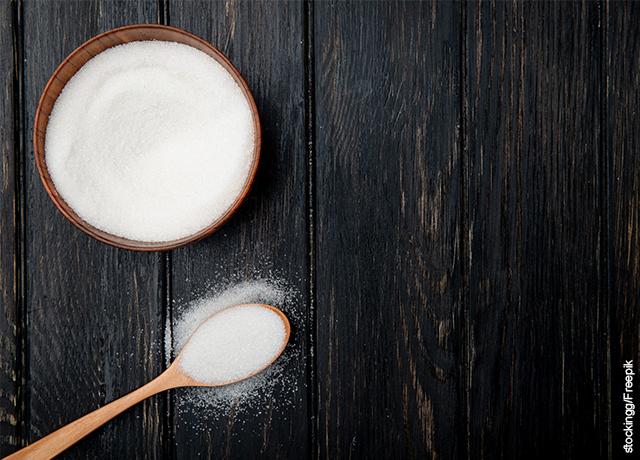 Foto de un tarro de azúcar blanca sobre una mesa de madera