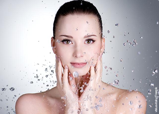 Foto de una mujer lavando su rostro con agua