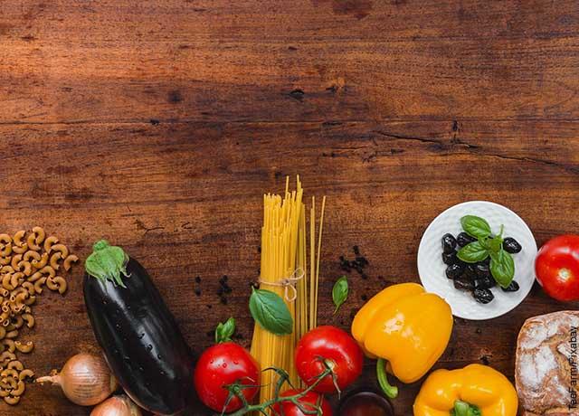 Foto de verduras y pastas sobre una mesa de madera