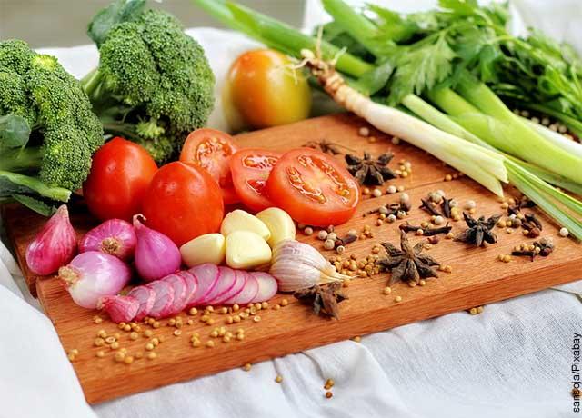 Foto de tomates, ajos, cebolla, brócoli sobre una tabla de picado