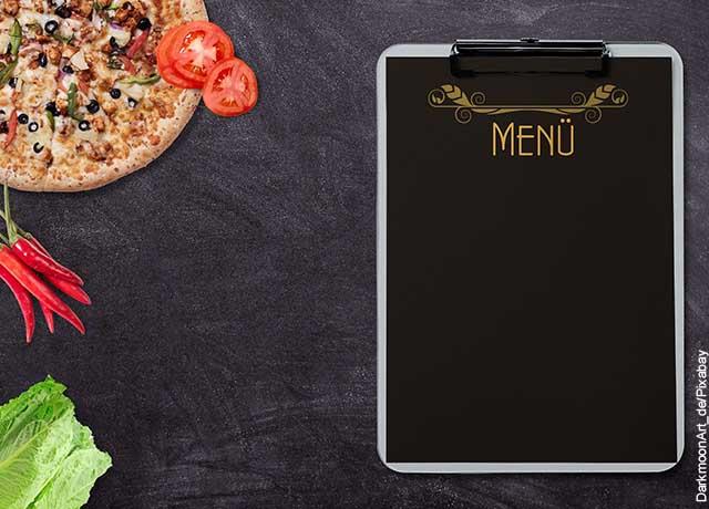 Foto de una tablet y una piza sobre una mesa oscura