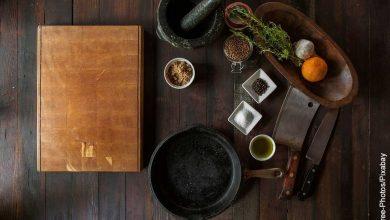 Foto de implementos de cocina y un libro sobre una mesa que muestra qué es una receta