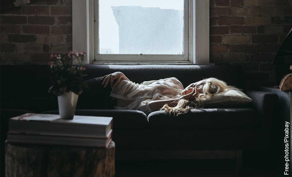 Foto de una mujer durmiendo sobre su sofá que muestra qué significan los sueños