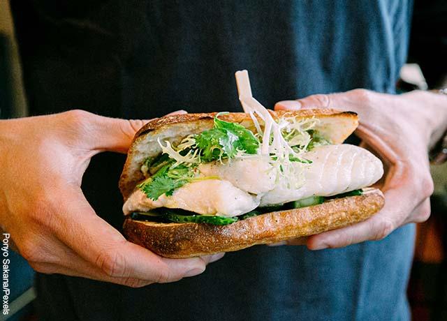 Foto de una persona con una hamburguesa de pescado
