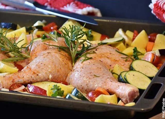 Foto de pollo crudo en una bandeja con verduras que muestra las recetas de comidas caseras