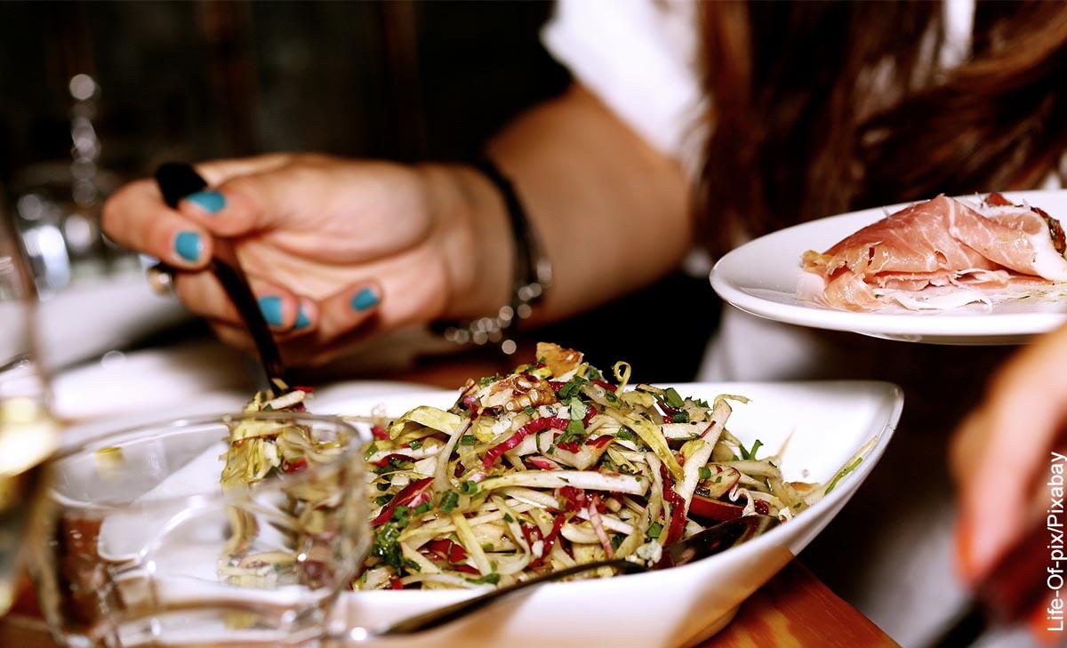 Foto de una mujer sirviendo ensalada que muestra las recetas para bajar de peso
