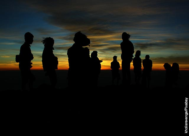 Foto de muchas personas al atardecer en un campo abierto