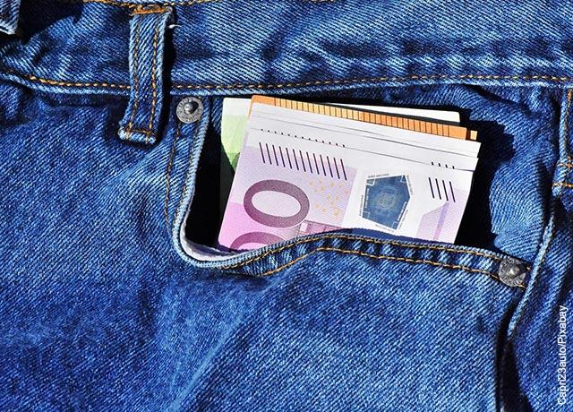Foto de billetes dentro del bolsillo de un jean