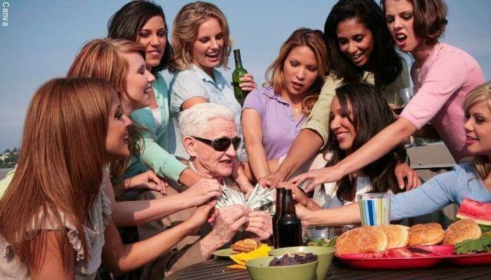 Foto de un hombre mayor rodeado de mujeres jóvenes