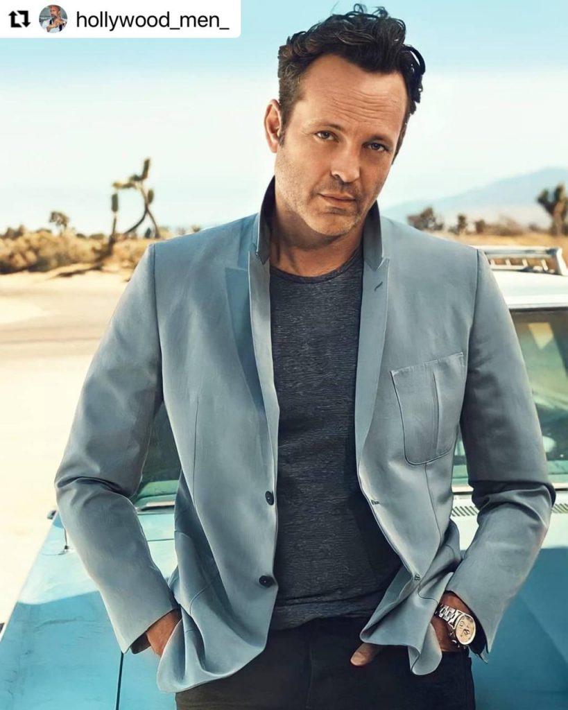 Vince Vauhgn posando con outfit sencillo de blazer azul, camiseta y pantalón, junto a su auto.