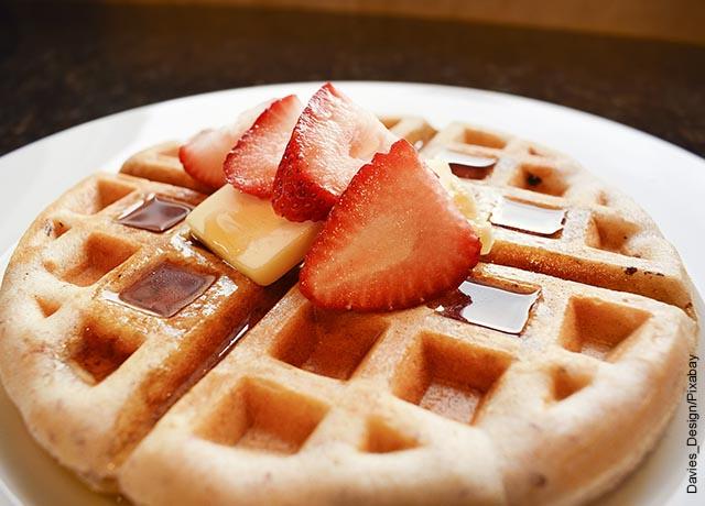Foto de unos waffles con miel y fresa servidos en un plato