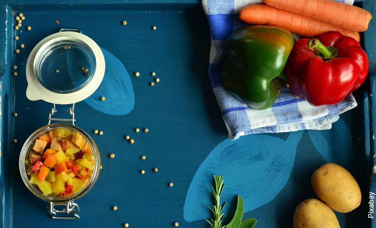Foto de verduras y papas sobre una mesa azul
