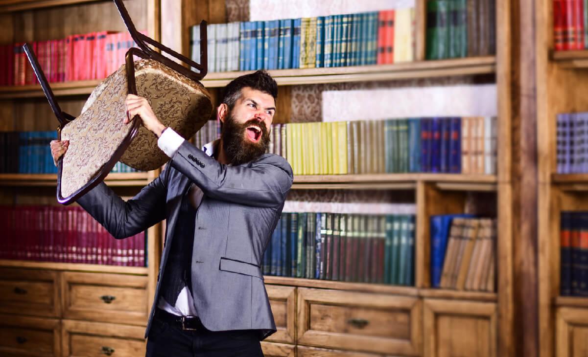 Foto de hombre enojado tirando una silla