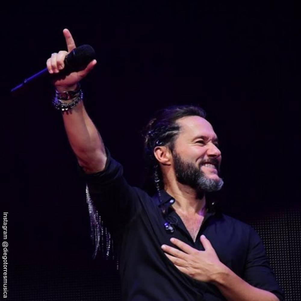 Foto de Diego Torres durante un concierto y levantando su mano derecha